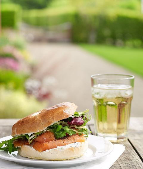 Summer food photographed outdoors at Newby Hall in Yorkshire. Smoked salmon and cream cheese bagel.