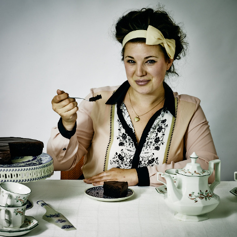 Young woman enjoying tea party with luxury chocolate cake. Retro.