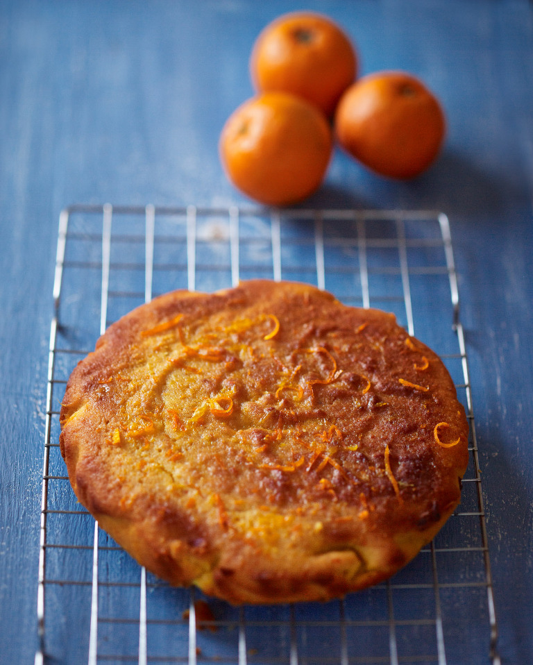 Food photography of Mediterranean orange polenta cake, blue background and oranges.