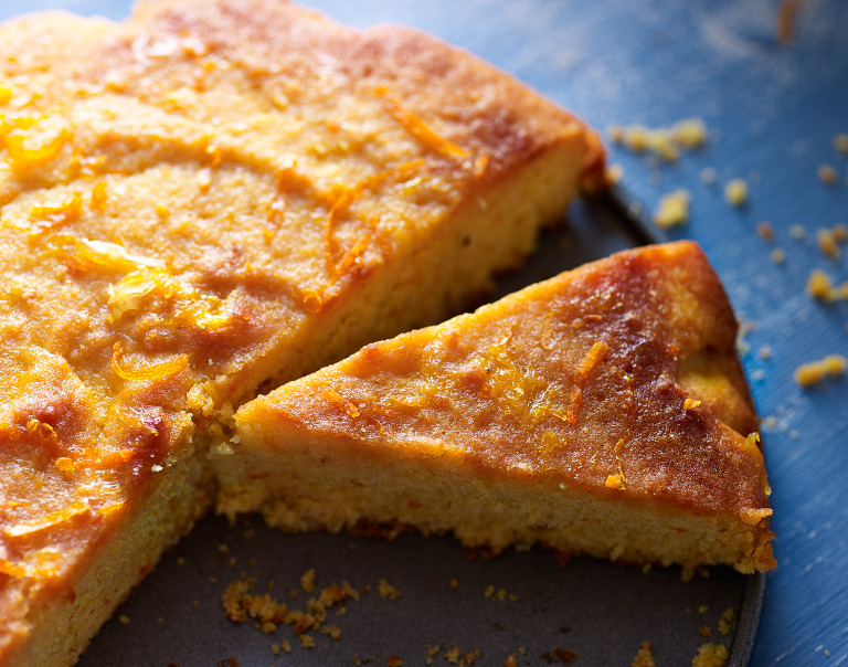 Food photograph of orange polenta cake, showing cut portion.
